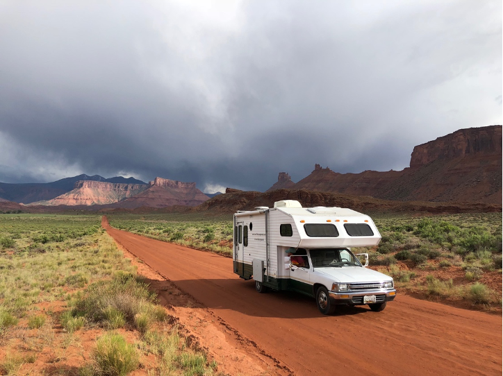 RV driving down dirt road with mountains